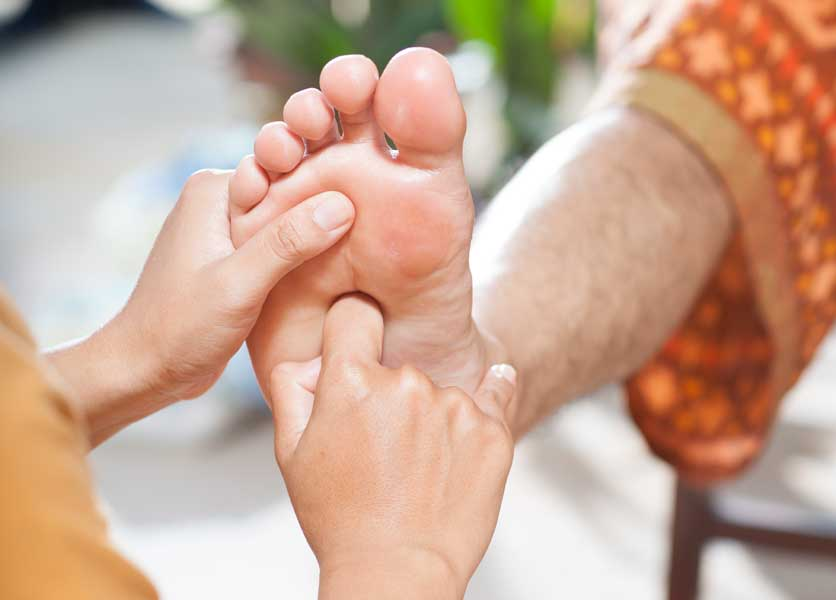 A foot being massaged during foot reflexology
