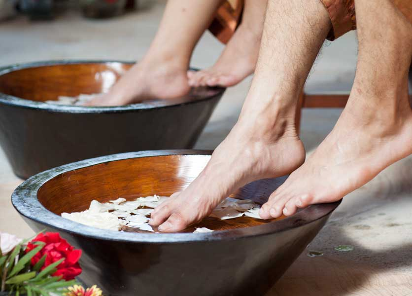 Two pairs of feet dipping in water during foot reflexology